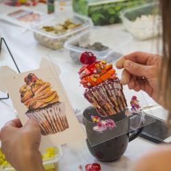 Лимоны на тарелке на переднем фоне и картины из мозаики с изображением пирожных на заднем фокус на картинах