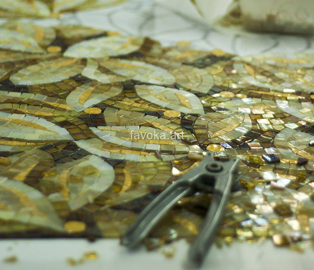 На заготовке из мозаики узор золотого цвета  - лепестки растений полностью симметричные, на заготовке лежит инструмент для раскалывания мозаики.