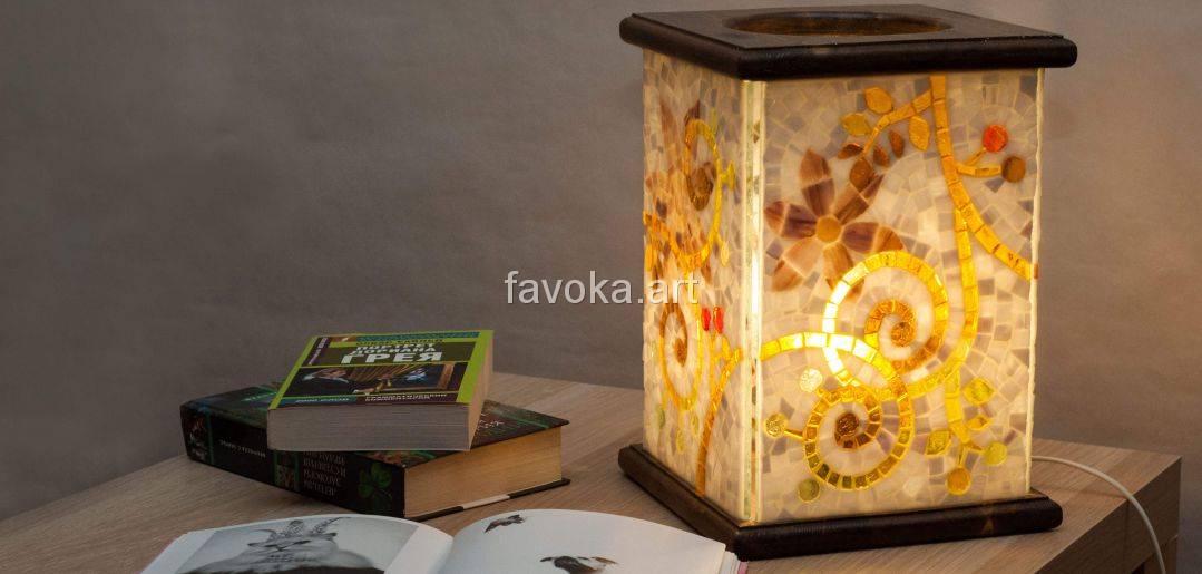 Стол, на нёмлежат книги друг на друге, рядом с ними ночник, стёкла, которого сделаны из мозаики, узор абстрактные ветки вишнёвого дерева и бутоны цветков