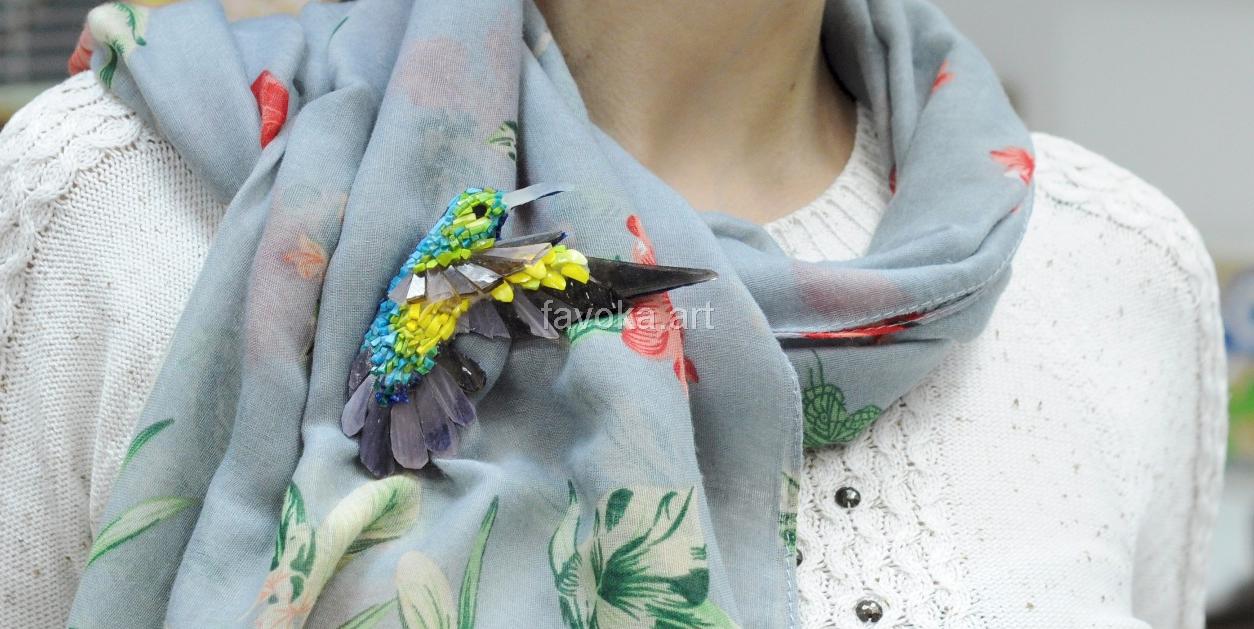 Маленькая колибри из мозаики, выполненная в технике микро-мозаики в голубом, зелёном, жёлтом и чёрных цветах.